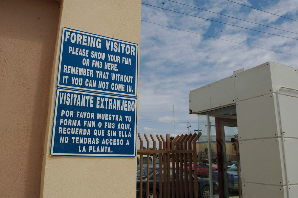 Matamoros, Mexico April, 2006: Bilingual signs outside a manufacturing plant across the U.S. border from Brownsville, TX .  ©Bob Daemmrich /
