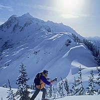 A skier hikes off-piste for a powder run near Mount Baker Ski Area, Washington.