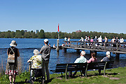 people waiting for the Ms Helena ferry over the Nieuwe Meer on the side of Amsterdam forrest by Wilgenlaantje
