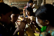 A family home in the slum surrounding Firozabad, renowned as the 'glass city', in Uttar Pradesh, northern India, has been transformed into a small-scale workshop where young girls are decorating the bracelets produced in factories nearby. Due to extreme poverty, over 20.000 young children are employed to complete the bracelets produced in the industrial units. This area is considered to be one of the highest concentrations of child labour on the planet. Forced to work to support their disadvantaged families, children as young as five are paid between 30-40 Indian Rupees (approx. 0.50 EUR) for eight or more hours of work daily. Most of these children are not able to receive an education and are easily prey of the labour-poverty cycle which has already enslaved their families to a life of exploitation. Children have to sit in crouched positions, use solvents, glues, kerosene and various other dangerous materials while breathing toxic fumes and spending most time of the day in dark, harmful environments. As for India's Child Labour Act of 1986, children under 14 are banned from working in industries deemed 'hazardous' but the rules are widely flouted, and prosecutions, when they happen at all, get bogged down in courts for lengthy periods. A ban on child labour without creating alternative opportunities for the local population is the central problem to the Indian Government's approach to the social issue affecting over 50 million children nationwide.