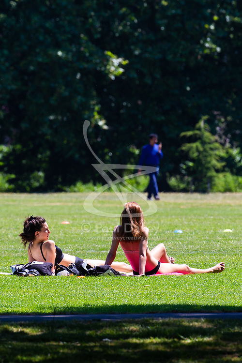 Two women soak up the sun in Regents Park, London, as the heatwave continues to grip the capital. London, June 29 2018.
