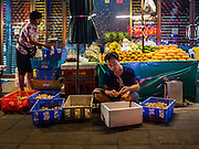 29 FEBRUARY 2016 - BANGKOK, THAILAND:  A sidewalk vendor in the Bangkok flower market sells mangos and fruit Monday. Many of the sidewalk vendors around Pak Khlong Talat, the Bangkok flower market, closed their stalls Monday. As a part of the military government sponsored initiative to clean up Bangkok, city officials announced new rules for the sidewalk vendors that shortened their hours and changed the regulations they worked under. Some vendors said the new rules were confusing and too limiting and most vendors chose to close Monday rather than risk fines and penalties. Many hope to reopen when the situation is clarified.   PHOTO BY JACK KURTZ
