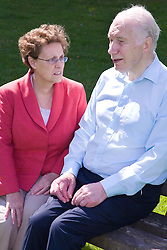 Older couple sitting on a park bench talking,