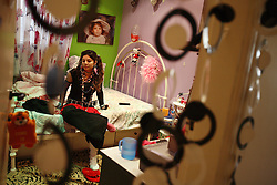 """Tatiana Hakim, 16, is seen in her room the day of the school holiday March Madness in Beirut, Lebanon, March 31, 2006. On this day kids dress up in crazy outfits to encourage school spirit. Her father is Sunni Muslim and mother is Maronite Christian. Although her mother technically converted to Sunni for the wedding, the family still celebrates Christian holidays, in addition to the Muslim ones. Tatiana identifies herself as """"half and half."""""""
