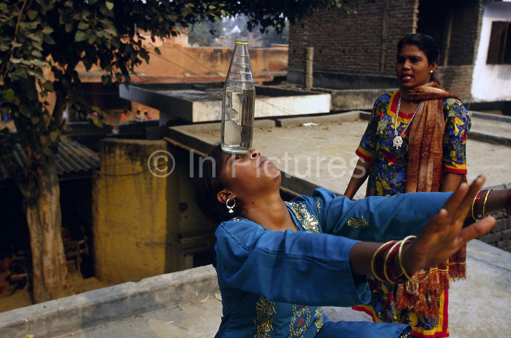 Reenu, 15, practices her contortions. Reenu and her family are trained by her mother, herself a former acrobat. The children, when babies, were stretched and contorted to make their bones pliable for the act. <br /> The Kathiputli Colony in the Shadipur Depot slum is home to hundreds of (originally Rajasthani) performers. The artistes who live here - from magicians, acrobats, musicians, dancers and puppeteers are often international renowed by always return to the Shadipur slum.