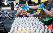 A volunteer distributes canola oil to local residents during a pop up grocery event at Powderhorn Park in Minneapolis, Minnesota, U.S., on Friday, July 24, 2020. Photographer: Ben Brewer/Bloomberg