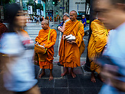09 NOVEMBER 2017 - BANGKOK, THAILAND: People walk past Buddhist monks waiting for people to give them alms in front of the Erawan Shrine on the 61st anniversary of the shrine's dedication. The Erawan Shrine is one of the most popular shrines in Bangkok. It was dedicated on November 9, 1956, after a series of construction accidents at what was then the Erawan Hotel (since torn down and replaced by the Grand Hyatt Erawan Hotel). The statue in the shrine is Phra Phrom, the Thai representation of the Hindu god of creation Brahma. It is a Hindu shrine popular with Thai and Chinese Buddhists because it is thought that making an offering to the Phra Phrom will bring good fortune.    PHOTO BY JACK KURTZ