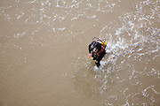 Looking down from above at professional diver on a beach about to enter the sea to work on the pier at Cromer, north Norfolk coast, England