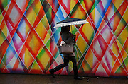 A woman walks through the rain in downtown Seattle in front of a colorful backdrop.<br /> <br /> Erika Schultz / The Seattle Times