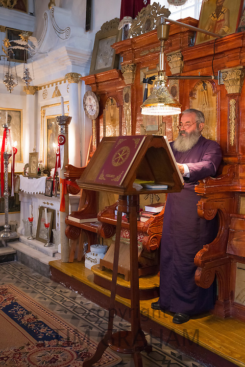 Greek Orthodox priest reading bible inside chapel of christian church at Krini, Corfu, , Greece
