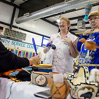 110814       Cable Hoover<br /> <br /> Gloria Cooeyate, left, holds a mirror for for Wanda Dreier, right and Jeanette Butler while Dreier tries on one of Cooeyate's necklaces during the Recycled Arts and Crafts Fair at the Gallup Community Service center Saturday.