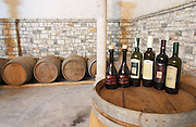 Bottles on top of a barrel, with barriques in the background: Raki me Arra grappa type of spirit, Trebiano Trebbiano, E bardha e Beratit, Kashmer, Shesh i Bardhe. Cobo winery, Poshnje, Berat. Albania, Balkan, Europe.