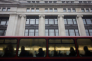 Silhouettes of anonymous bus commuters and a large corporate building during damp, gloomy weather in central London. Sitting with strangers on the top deck of the bus, the public travellers apear as dark shapes beneath the tall Ionic columns and pillars of a large insurance company. The people are riding south towards Holborn where offices and headquarters are located.