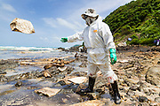02 AUGUST 2013 - KOH SAMET, RAYONG, THAILAND: A worker throws absorption pads into the oil fouled waters off of Ao Prao beach during clean up efforts after an oil spill. About 50,000 liters of crude oil poured out of a pipeline in the Gulf of Thailand over the weekend authorities said. The oil made landfall on the white sand beaches of Ao Prao, on Koh Samet, a popular tourist destination in Rayong province about 2.5 hours southeast of Bangkok. Workers from PTT Global, owner of the pipeline, up to 500 Thai military personnel and volunteers are cleaning up the beaches. Tourists staying near the spill, which fouled Ao Prao beach, were evacuated to hotels on the east side of the island, which was not impacted by the spill. Officials have not said when Ao Prao beach would reopen. PTT Global Chemical Pcl is part of state-controlled PTT Pcl, Thailand's biggest energy firm.    PHOTO BY JACK KURTZ