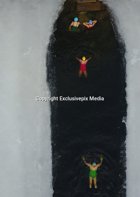 SHENYANG, CHINA - JANUARY 17: <br /> <br /> Winter Swimmers Brace Against The Chill<br /> <br /> Aerial view of winter swimmers dressed in colorful swimsuits swimming at an artificial lake of Beiling Park on January 17, 2017 in Shenyang, Liaoning Province of China. Winter swimmers brace against the chill and stick to work out at Beiling Park in winter.<br /> ©Exclusivepix Media