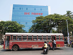 Bus with smart new office tower block in background, Mumbai.