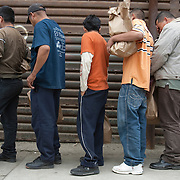Undocumented migrants line up along the border fence for deportation back to Mexico after being caught entering the country illegally. Please contact Todd Bigelow directly with your licensing requests.