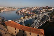 A morning aerial panorama of a tram crossing the Ponte de Dom Luis I bridge with the city of Porto behind on the River Douro and a foreground of warehouse rooftops, on 20th July, in Porto, Portugal. The Dom Luís I or Luiz I Bridge is a double-decked metal arch bridge that spans the Douro River between the cities of Porto and Vila Nova de Gaia in Portugal. At the time of construction its span of 172 m was the longest of its type in the world.