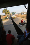 ROYAL CAMBODIAN RAILWAYS. The journey from Phnom Penh to Battambang is the last working route. A passenger train, operates only at weekends. A Czech made diesel locomotive, leaves the capital Saturday morning, arriving in Battambang 22 hours later in the dead of night, and returns on Sunday. Max speed is about 30kmh, often slower due to the track's terrible condition. Carriages are dilapidated, with holes in the floor and only spaces for windows. Passengers sit or sleep on hardwood bench seats, hammocks, or on the floor of cargo carriages. The drivers, controllers & guards add to their small monthly pay by charging for local passengers and cargo; from motor bikes and local produce to timber loaded aboard at the 30 stations along the route. This together with other trains and farm vehicles further slows the journey. In rural areas, the track is a lifeline, and used for local transport on 'bamboo trains' powered by belt-motors, or pushcarts. Boom towns, with a 'goldrush mentality' near the rapidly depleted rainforest, are a hive of activity, with logging as their resource, where children workers even gamble away their earnings on cardgames. In the city, the railway has a life of its own, where people live and work nearby or on the track itself. Market stalls, restaurants, chairs and tables, are removed only briefly, when the infrequent train passes!///Train crosses a road with traffic
