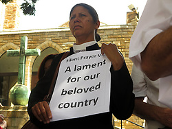 Wednesday 2nd October 2016.<br /> St. George's Cathedral,<br /> Cape Town,<br /> Western Cape,<br /> South Africa.<br /> <br /> #SaveSouthAfrica Silent Prayer Vigil In Cape Town!<br /> <br /> A Religious Leader stands holding a placard that reads 'A lament for our beloved country' as she and other Concerned Citizens and Religious Leaders stand together in silent protest on the steps of St. George's Cathedral in Cape Town.<br /> <br /> Concerned Religious Leaders and other South Africans gathered together in silent protest in support of the call to #SaveSouthAfrica from 'the acute social crisis that has been brought about by corruption, mismanagement and political intrigue' as reported nationwide in the news. The campaign was formed under the banner of holding government leaders accountable to the Constitution and the values they have pledged to uphold as representatives of the people. The #SaveSouthAfrica Silent Prayer vigil was held at St. George's Cathedral in Cape Town, South Africa on Wednesday 2nd November 2016.<br /> <br /> Picture By:  Mark Wessels / RealTime Images.