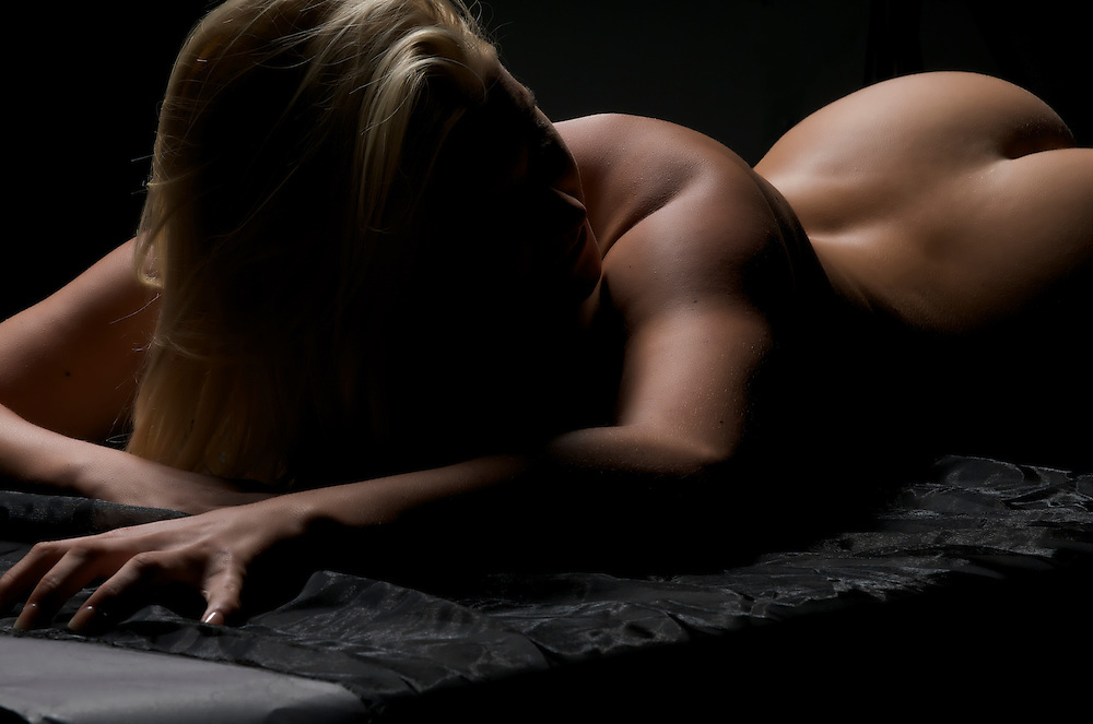 Youn caucasian blonde woman posing nude in dim light.