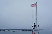 The English flag on a fishing boat flutters on a faint breeze, with an old harbour jetty and a returning boat from the Northumbrian North Sea, on 25th September 2017, in Amble, Northumberland, England.
