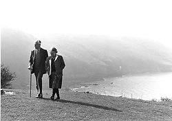 Elderly couple walking along cliff top,