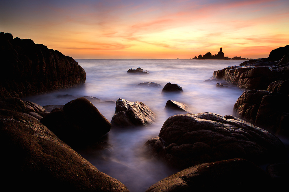 Misty water surrounding the rocks at Corbiere lighthouse, with an orange sky at sunset, Jersey, Channel Islands