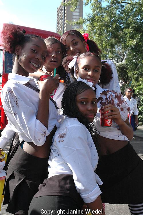 Group of black teenaged school girls posing in street Notting Hill Gate London.