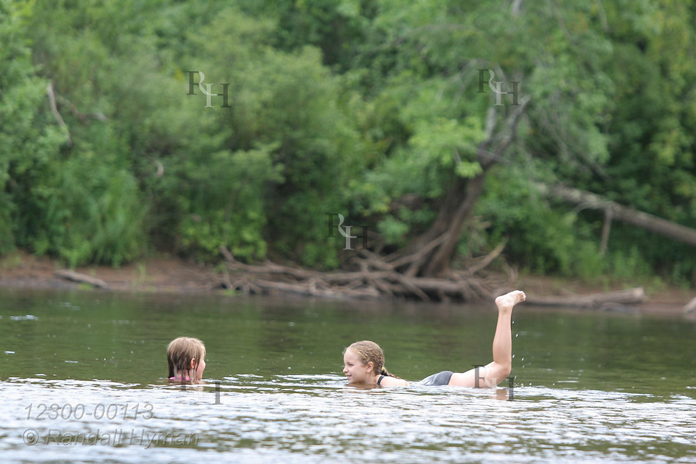 Two young girls play in shallow, wide section of St. Croix River in St. Croix State Park, part of the St. Croix National Scenic Riverway; Minnesota.