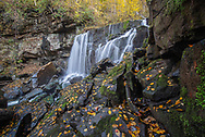 Wolf Creek Falls in the New River Gorge of West Virginia is framed by rocks and trees bedecked with colorful yellow autumn foliage.