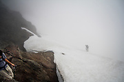 Two climbers descend onto a snow field in the fog on an ascent of Tomyhoi Peak, Mount Baker Wilderness, Washington.