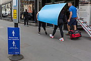 Staff with visual merchandising supplier Bright Leaf carry blue boards and materials  back to their West End premises, on 24th July 2020, in London, England.