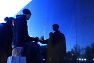 Visitors pause to view a name engraved on the wall of the Vietnam Veterans Memorial, Saturday, April 16, 2016, in Washington. (Phelan M. Ebenhack via AP)