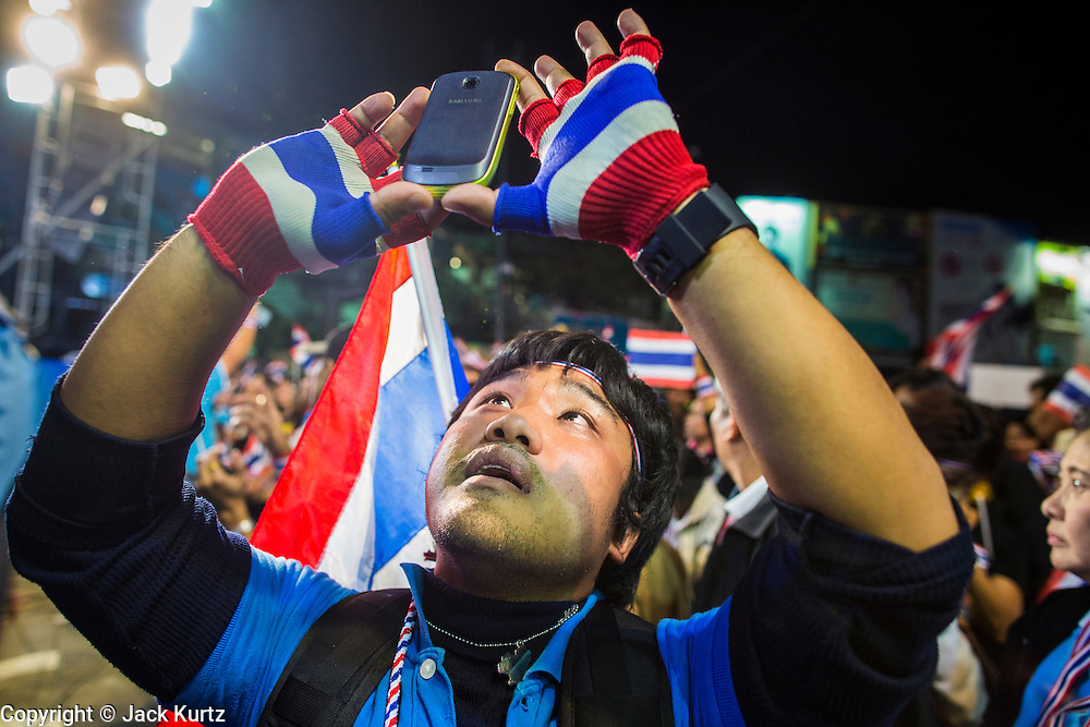 24 JANUARY 2014 - BANGKOK, THAILAND:  A Thai anti-government protestor tries to photograph protest leader Suthep Thaugsuban with his smart phone when Suthep walked on stage at the Shutdown Bangkok Pathum Wan stage. Shutdown Bangkok has been going for 12 days with no resolution in sight. Suthep, the leader of the anti-government protests and the People's Democratic Reform Committee (PDRC), the umbrella organization of the protests,  is still demanding the caretaker government of Prime Minister Yingluck Shinawatra resign, the PM says she won't resign and intends to go ahead with the election.   PHOTO BY JACK KURTZ
