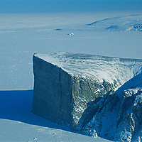 A huge granite prow cleaves two frozen fjords on the northeast coast of Canada's Baffin Island, with Baffin Bay in the background.