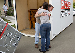 Homeowner receives a hug from a neighbor sad to see him move.  He and his partner lost their home in 2009 to foreclosure due to a combination of job loss, adjustable loan payments doubling and  home value under water nearly fifty percent. Photo by Kim Kulish