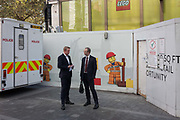 Two businessmen hold a conversation in front of a construction hoarding for a new Lego store, on 23rd September 2016, in Leicester Square, central London, England. Standing at the rear of a nearby police vehicle, the two men wear suits while in the background, the Lego workmen make a humorous moment.