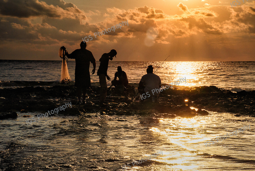 Silhouette of a group of Fishermen, cast net fishing from the rocks on the beach in Boca Raton, Florida