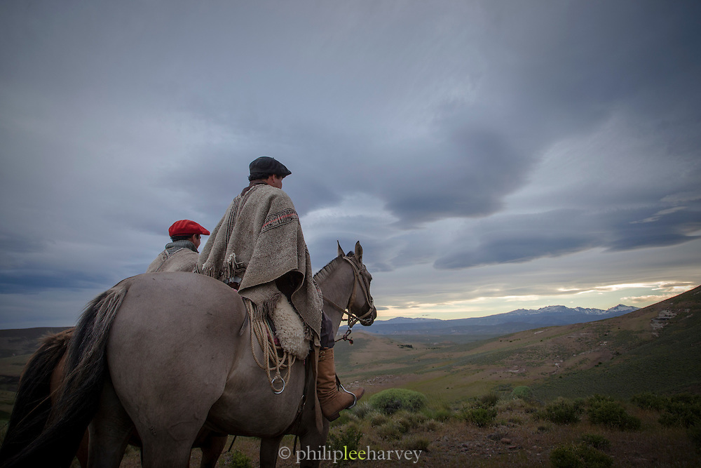 Gauchos on horseback overlooking the plains in twilight, Estancia Huechahue, Patagonia, Argentina, South America