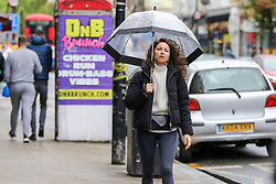 © Licensed to London News Pictures. 16/05/2021. London, UK. A woman shelters from light rain beneath an umbrella in north London. More rain is forecast for the South East of England this week. Photo credit: Dinendra Haria/LNP