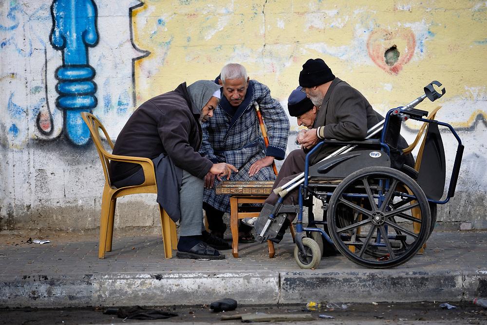 Old men play a game on a sidewalk in Gaza.