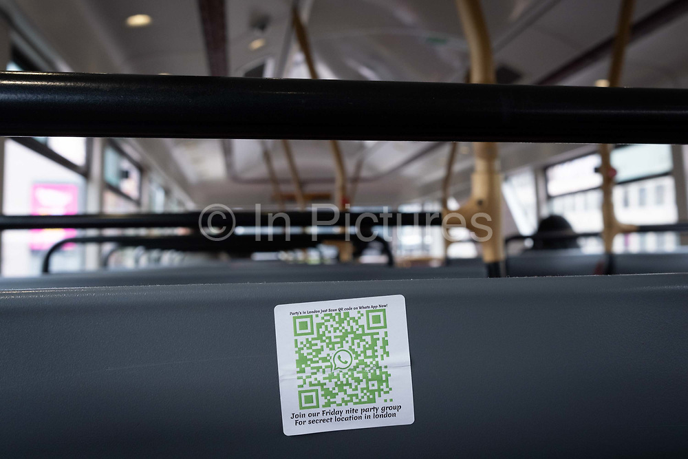 On the back of a bus seat, a discreet sticker shows a QR Code which advertises an illegal party,  during the Coronavirus pandemic, a time when the government and police are having to shut-down social gatherings where distances are being ignored, on 29th August 2020, in London, England.