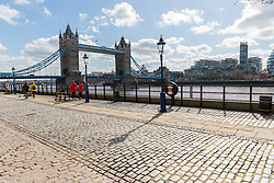 © Licensed to London News Pictures. 16/03/2020. London, UK. A very quiet and empty scene next to Tower Bridge at lunchtime today which is normally busy with tourists at this time (12:15pm). New cases and fatalities resulting from the COVID-19 strain of the Coronavirus continue to be reported daily in the UK with major sporting fixtures cancelled and people advised to stay at home if they have a cough and high temperature. Photo credit: Vickie Flores/LNP