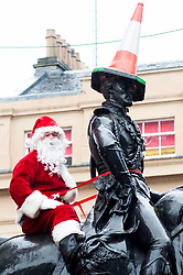 Dressed as Santa Claus, Ricky McConnell sits behind the Duke of Wellington on the statue in Royal Exchange Square Glasgow<br />  21 December 2015<br />  Copyright Paul David Drabble<br />  www.pauldaviddrabble.co.uk