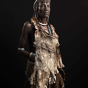 Portrait of Shawki Ayke.<br /> <br /> Hamer woman wear dried goat hides. They also decorate themselves with jewellery that include bracelets made of copper or the more expensive metal from diff springs of cars. This metal is becoming so expensive that younger Hamer woman cannot afford to buy many. These bracelets are seen as as sign of wealth.