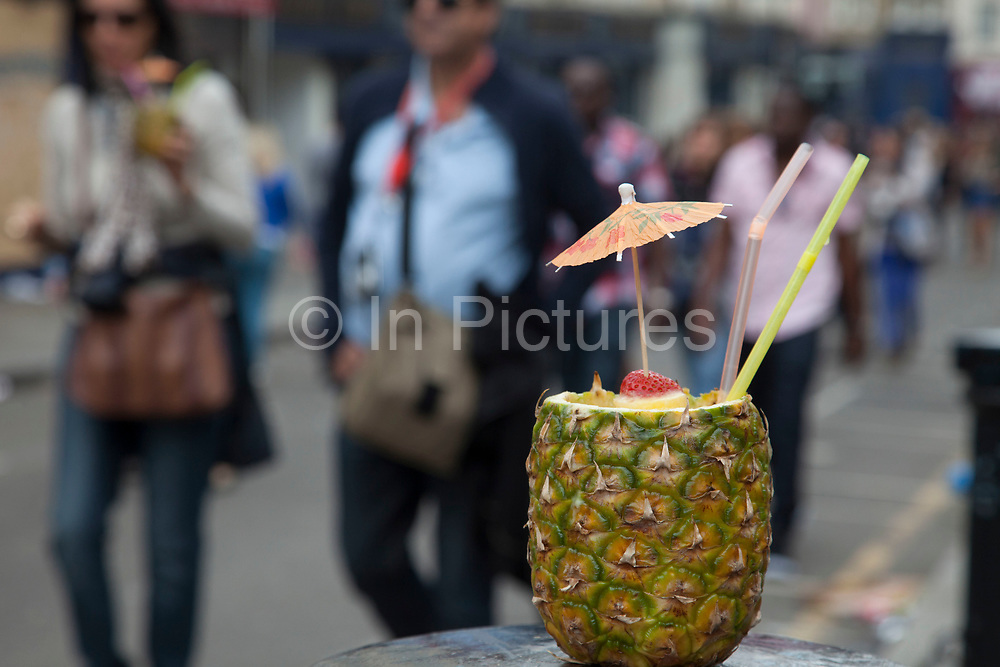Pineapple drink at Notting Hill Carnival in West London. The Notting Hill Carnival is an annual event which since 1964 has taken place each August, over two days (the August bank holiday Monday and the day beforehand). It is led by members of the West Indian / Caribbrean community, particularly the Trinidadian and Tobagonian British population, many of whom have lived in the area since the 1950s. The carnival has attracted up to 2 million people in the past, making it the second largest street festival in the world. The celebration centres around a parade of floats, dancers and sound systems.