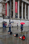 A family shelters beneath umbrellas during a sudden downpour outside the National Gallery in Trafalgar Square, on 13th August 2018, in London, England.