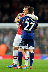 Arsenal Forward Lukas Podolski (GER) hugs Fulham Defender Sascha Riether (GER) after Arsenal win the match 2-0 - Photo mandatory by-line: Rogan Thomson/JMP - Tel: Mobile: 07966 386802 - 18/01/14 - SPORT - FOOTBALL - Emirates Stadium - Arsenal v Fulham - Barclays Premier League.