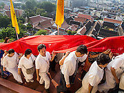 30 OCTOBER 2014 - BANGKOK, THAILAND: People carry the red cloth that will be around the chedi up the hill to the chedi during the parade marking the start of the annual temple fair at Wat Saket. Wat Saket is on a man-made hill in the historic section of Bangkok. The temple has golden spire that is 260 feet high which was the highest point in Bangkok for more than 100 years. The temple construction began in the 1800s in the reign of King Rama III and was completed in the reign of King Rama IV. The annual temple fair is held on the 12th lunar month, for nine days around the November full moon. During the fair a red cloth (reminiscent of a monk's robe) is placed around the Golden Mount while the temple grounds hosts Thai traditional theatre, food stalls and traditional shows.   PHOTO BY JACK KURTZ